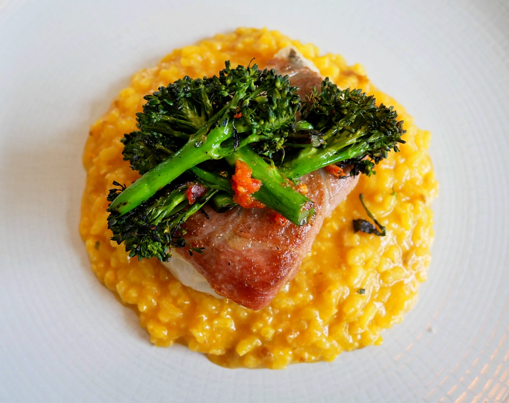 Roasted Hake wrapped in Serrano Ham, with a Saffron and Chorizo Risotto with Chargrilled Brocolli